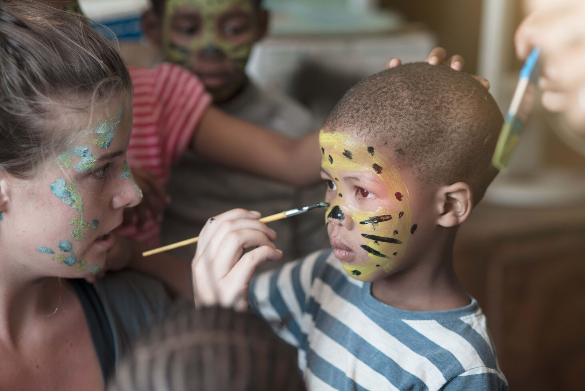 Volunteers painting childrens faces